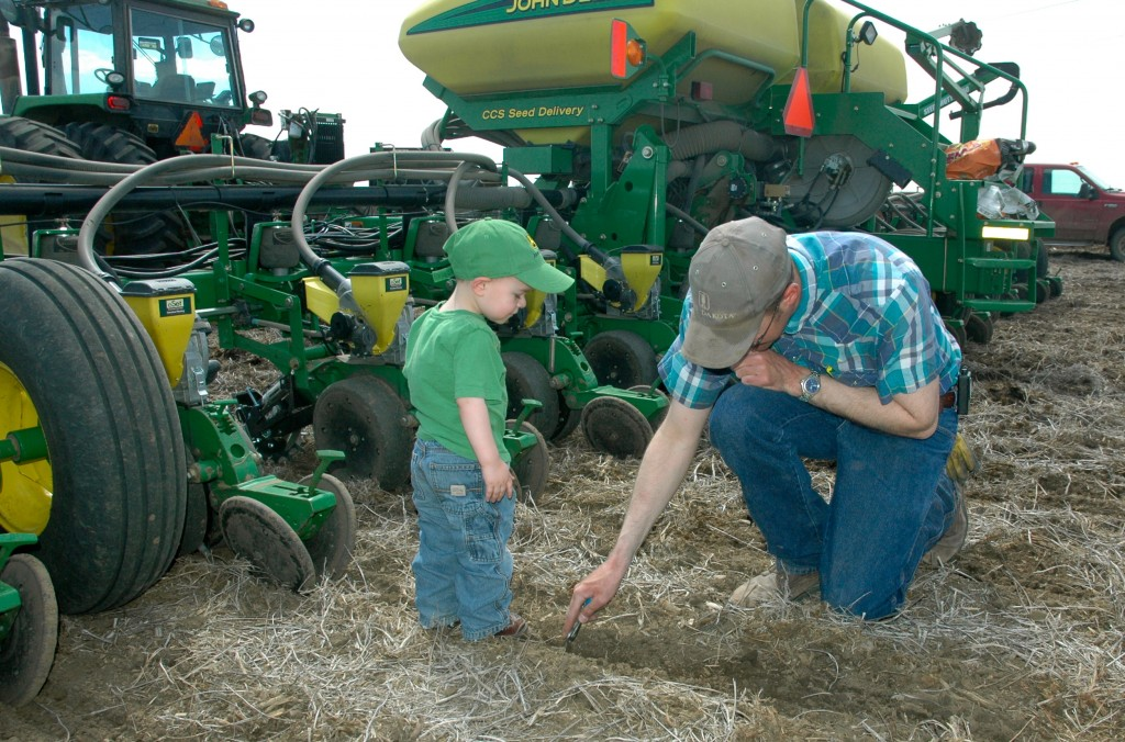 SDCUC president Brian Smith and his son examine the soil while utilizing no-till to plaint this year's corn crop.
